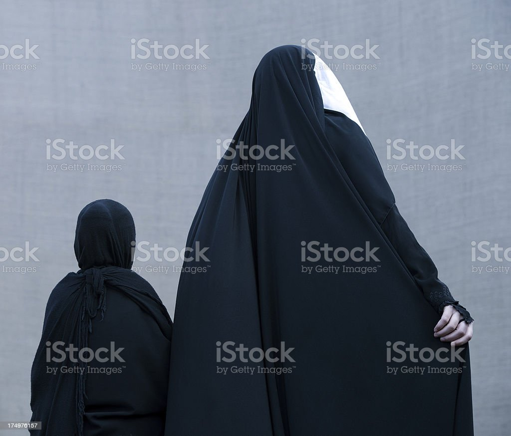 Muslim woman walking with her daugther stock photo