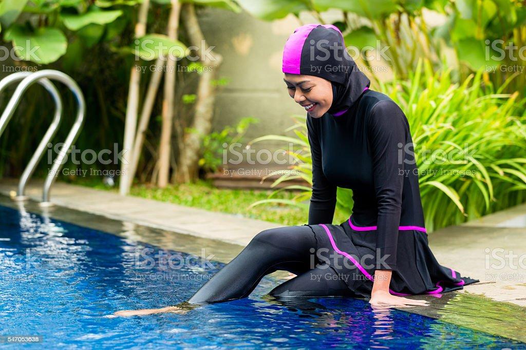 Muslim woman wearing Burkini swimwear at pool stock photo