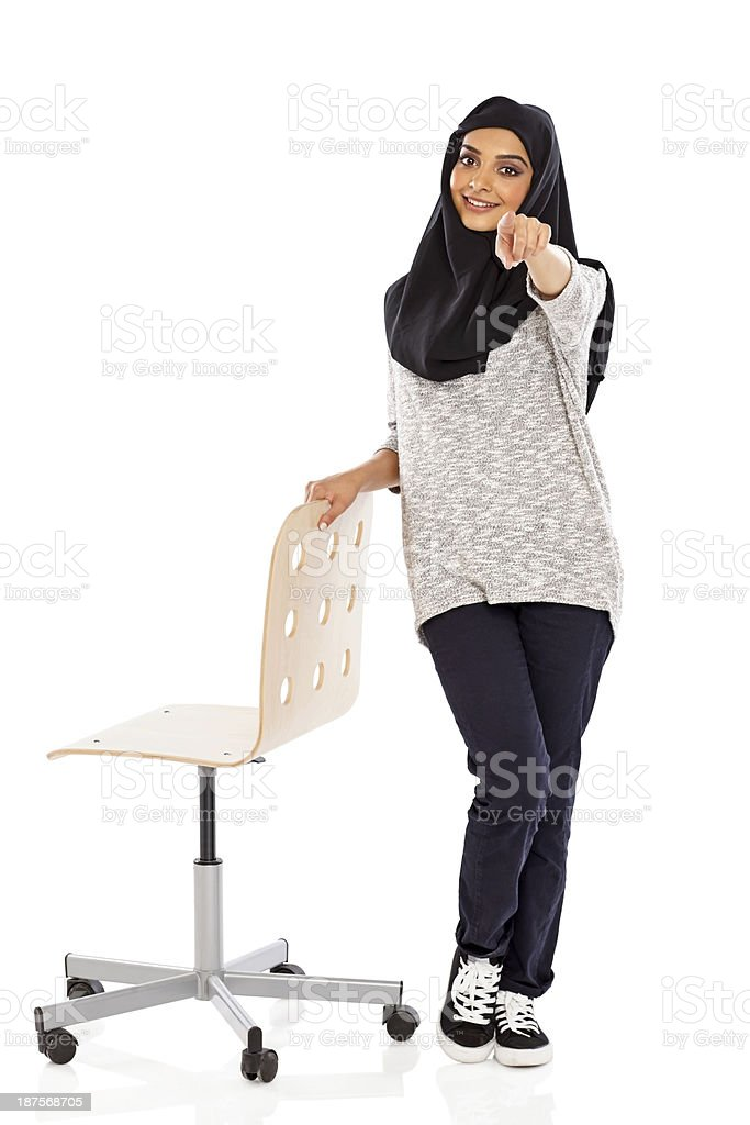 Muslim woman with a chair pointing at camera royalty-free stock photo