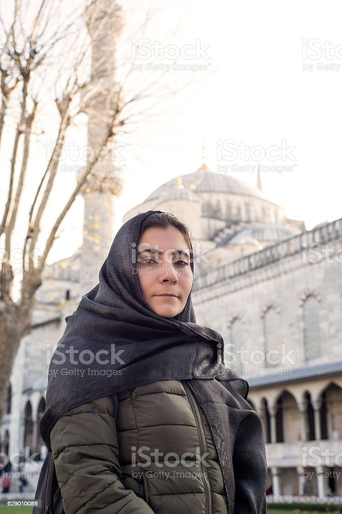 Muslim Woman With Blue Mosque Behind Her. stock photo