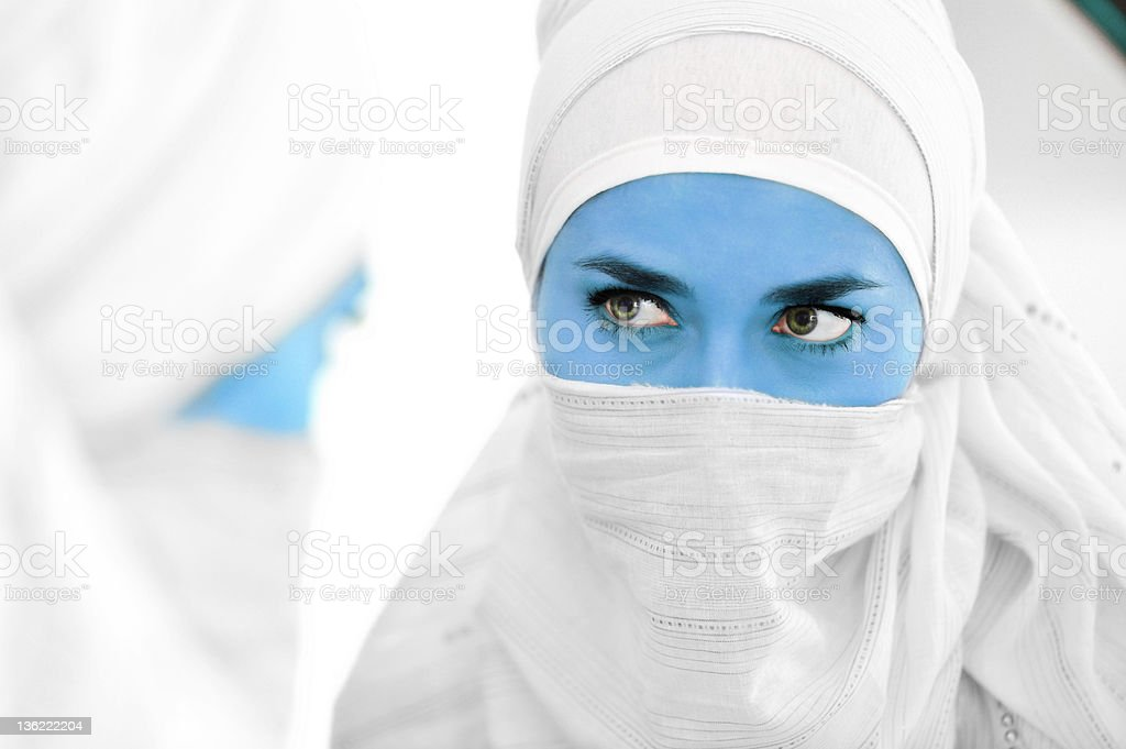 Muslim woman with blue skin as alien at mirror, concept royalty-free stock photo