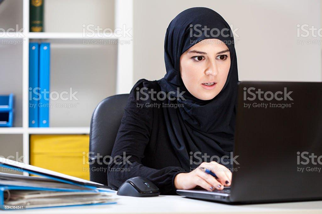 Muslim woman working on laptop stock photo