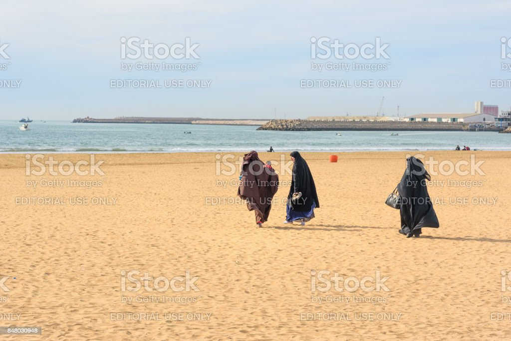 Muslim women in black long gowns walking on the beach. Agadir. Morocco stock photo