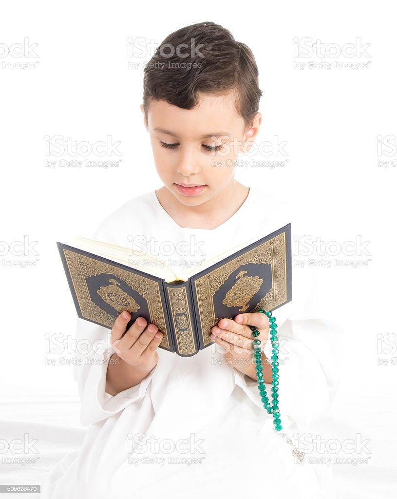 Muslim young kid reading Quran stock photo