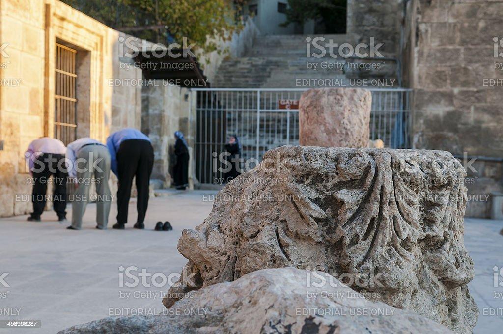 Muslims praying behind Roman ruins in Amman, Jordan royalty-free stock photo