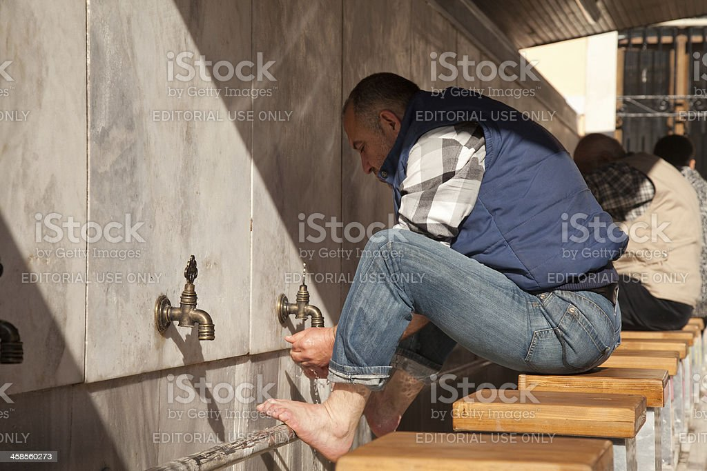 Muslims wash their feet at the fountain royalty-free stock photo