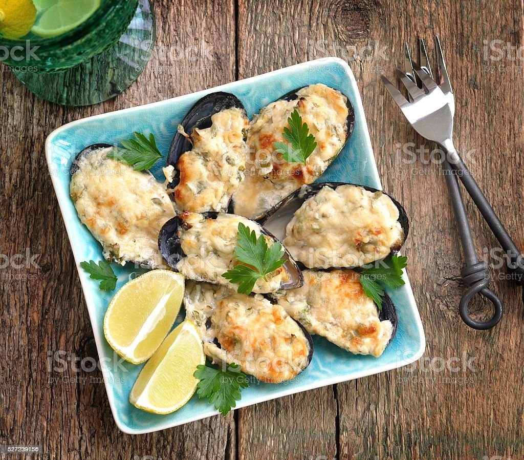 Mussels baked in cheese sauce with garlic stock photo