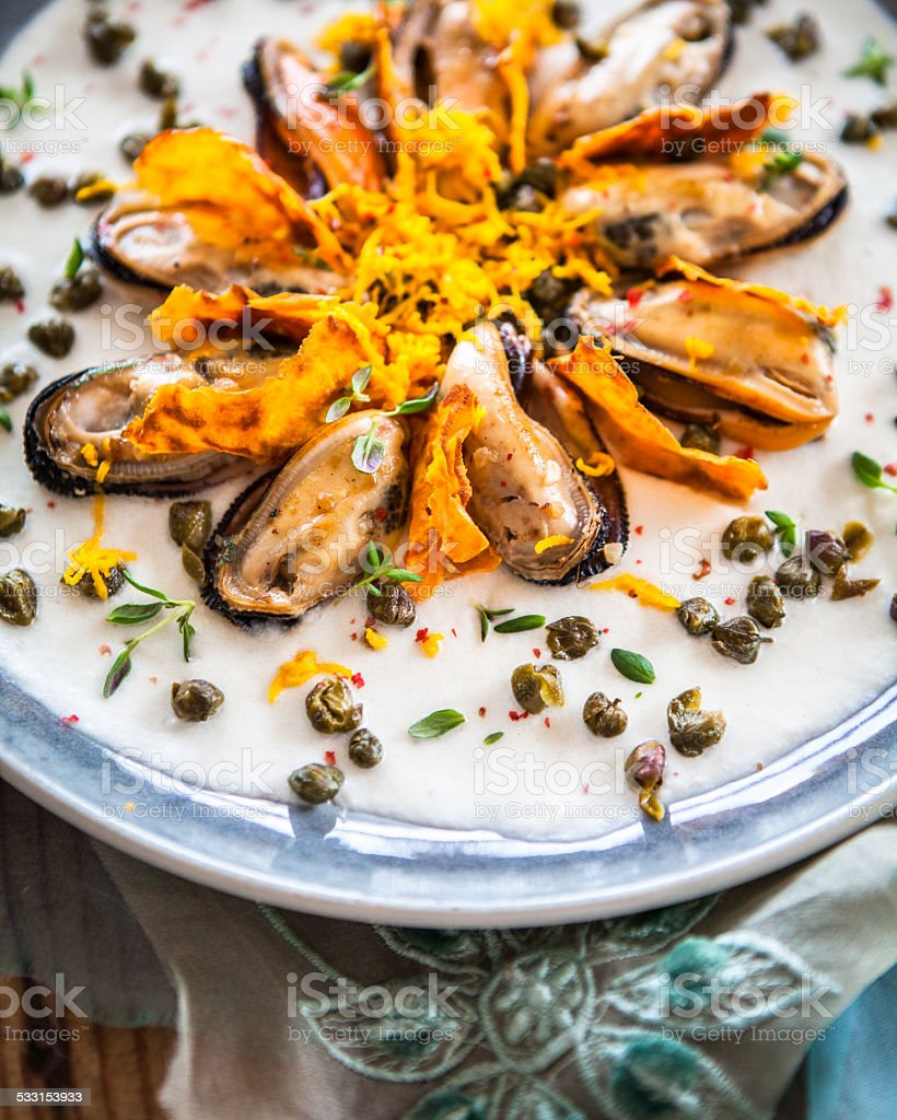 Mussels in cauliflower pur��e, fried capers and sweet potato chips stock photo