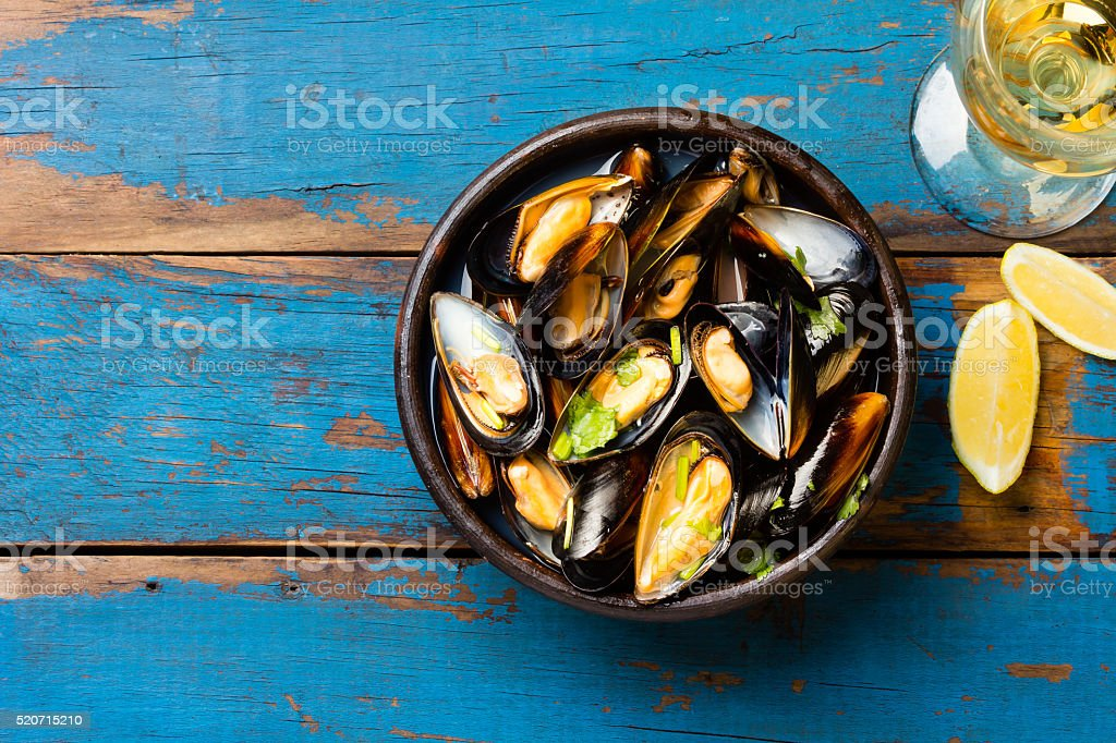 Mussels in clay bowl, glass of white wine and lemon stock photo