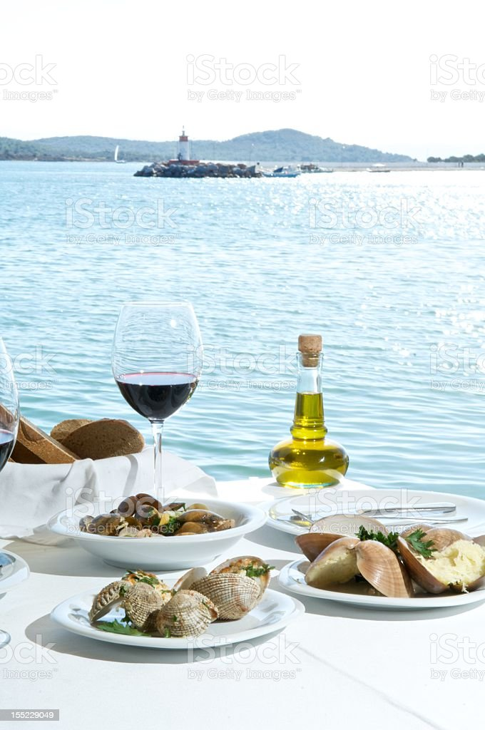 Mussels served on seaside restaurant with wines royalty-free stock photo