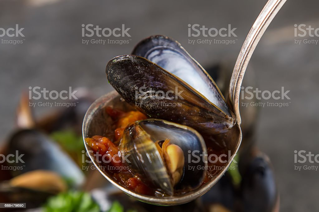 Mussels with herbs in a copper bowl. Seafood. Food at the shore of the French Sea. Dark background. stock photo