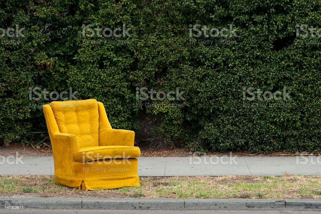 Mustard chair on a curb near a hedge stock photo