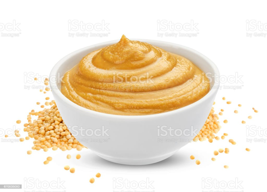 Mustard sauce in bowl and mustard seeds isolated on white background stock photo