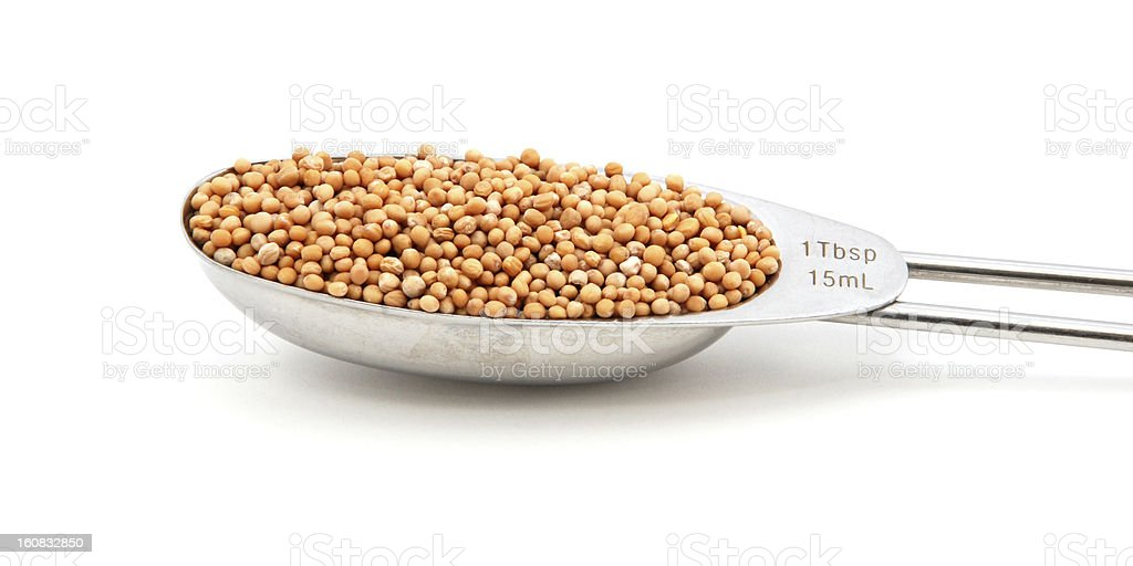 Mustard seeds measured in a metal tablespoon royalty-free stock photo
