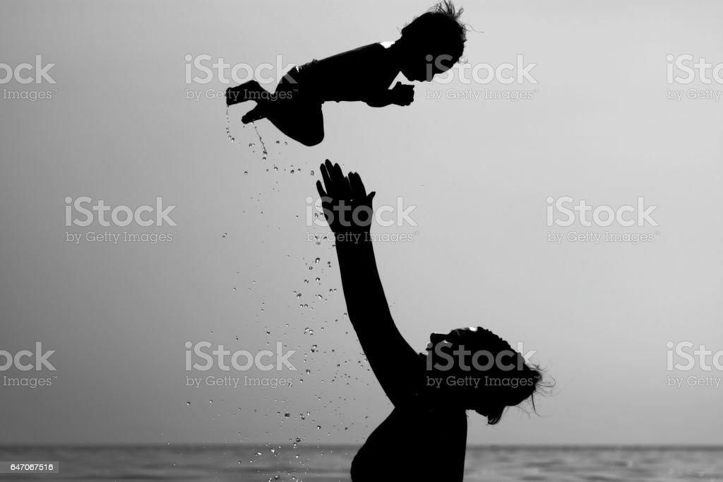 Mutter wirft Sohn in die Luft stock photo