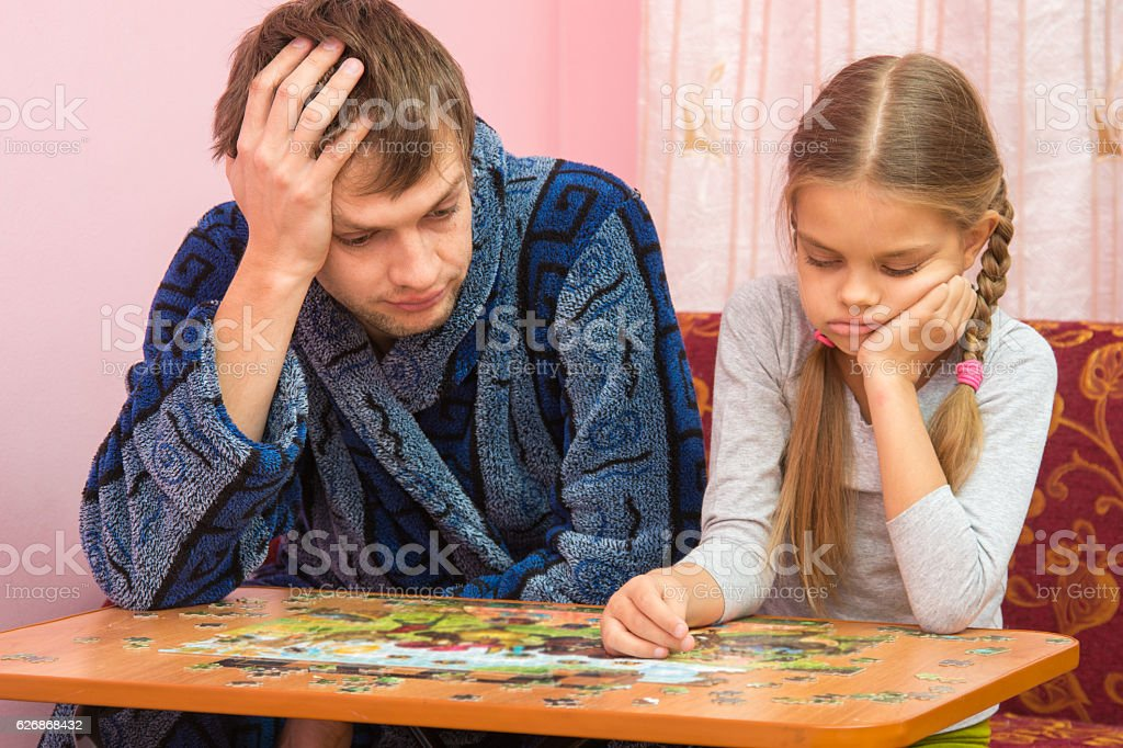 My daughter collects a picture from puzzles, tired dad sitting stock photo