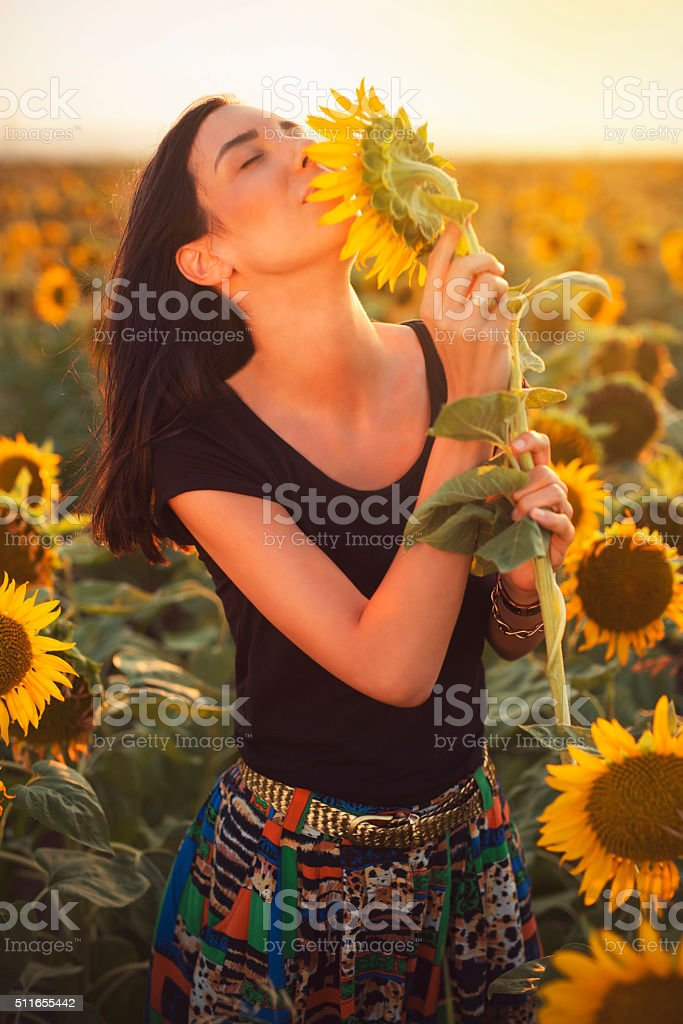 Portrait of a beautiful black-haired woman enjoying the scent of a...