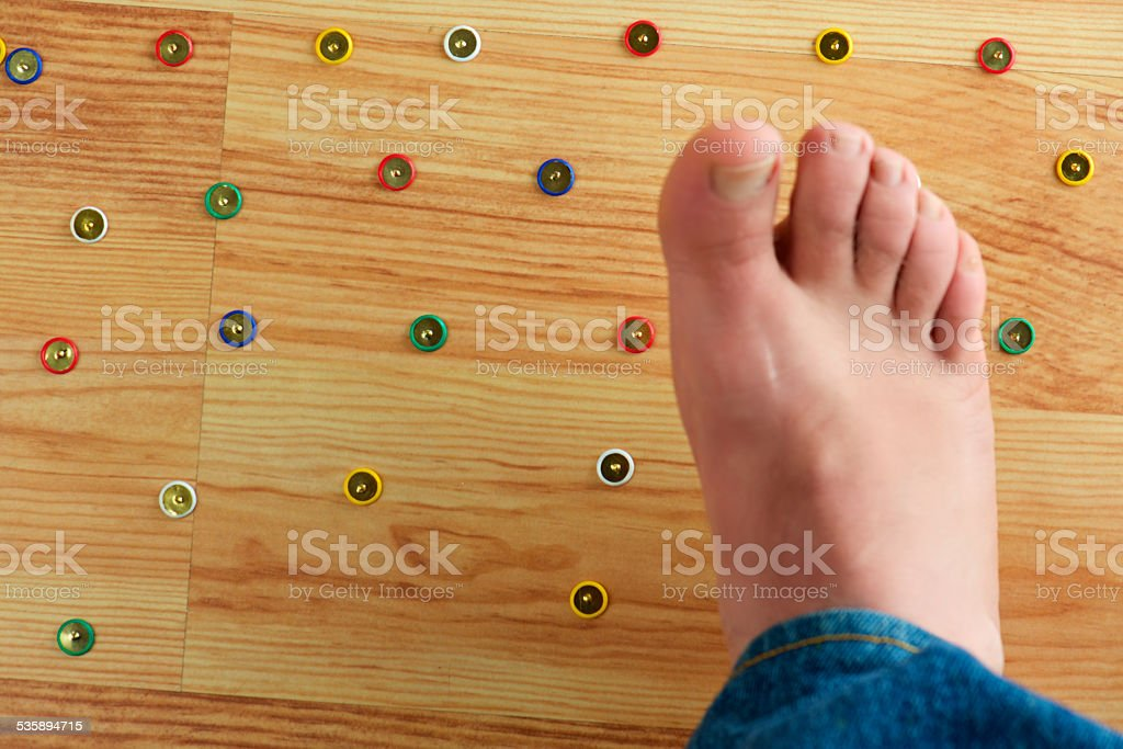 my foot is in danger! Push pins trap stock photo