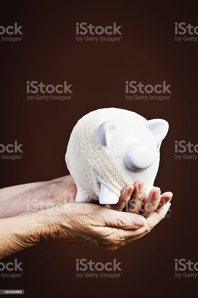 My savings are not safe: old hands hold bandaged piggybank royalty-free stock photo