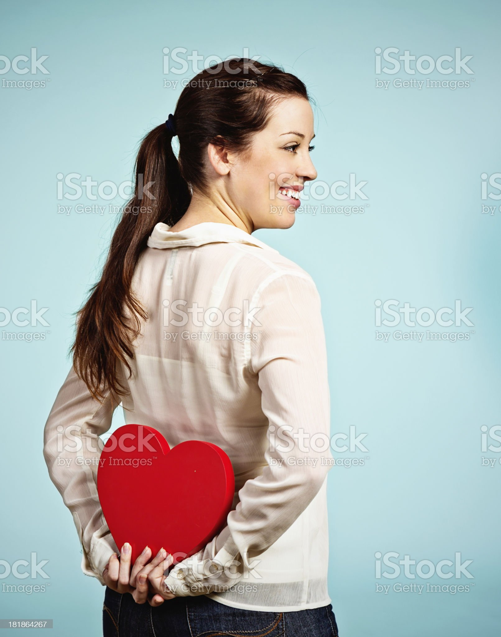 My secret love! Pretty brunette hides Valentine heart royalty-free stock photo