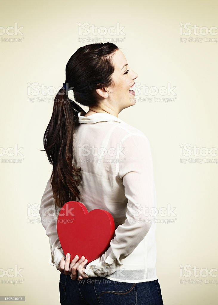 My secret love! Pretty woman hides Valentine behind her back royalty-free stock photo