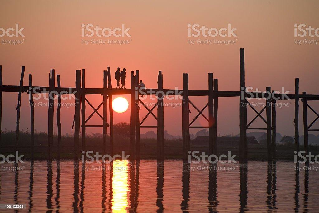 Myanmar: Crossing U Bein Teak Bridge at Sunset stock photo