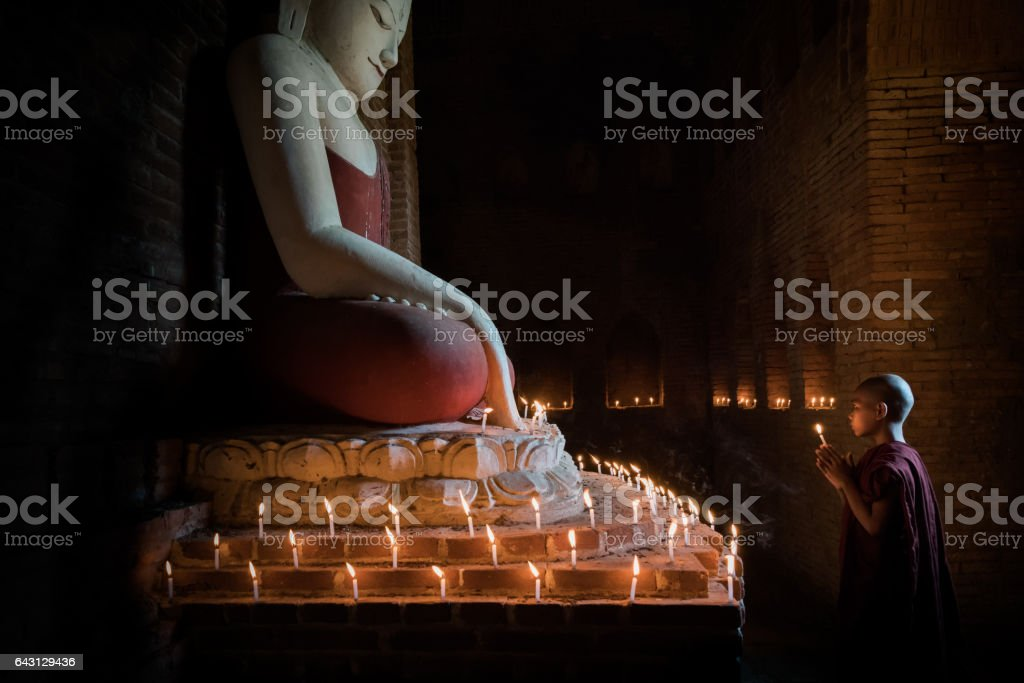 Myanmar Novice Monk praying in front of illuminated Buddha Statue stock photo