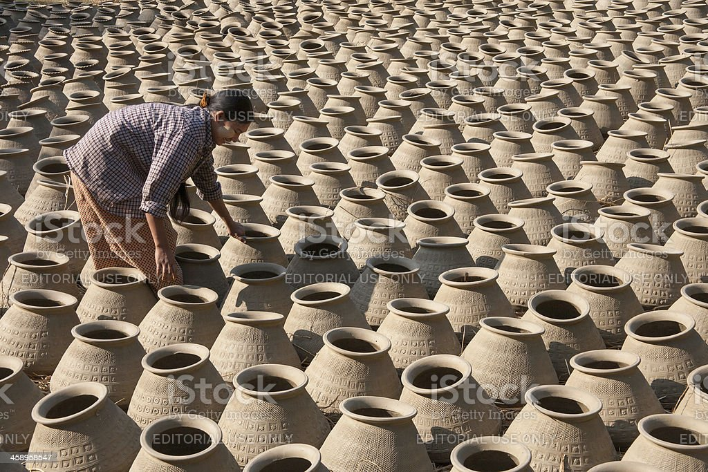 Myanmar: Woman Inspecting Water Jugs in Pottery Yard royalty-free stock photo