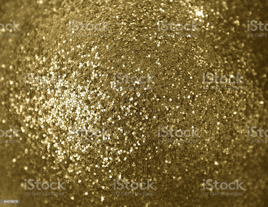 Myriad of golden spangles in a pile from above stock photo