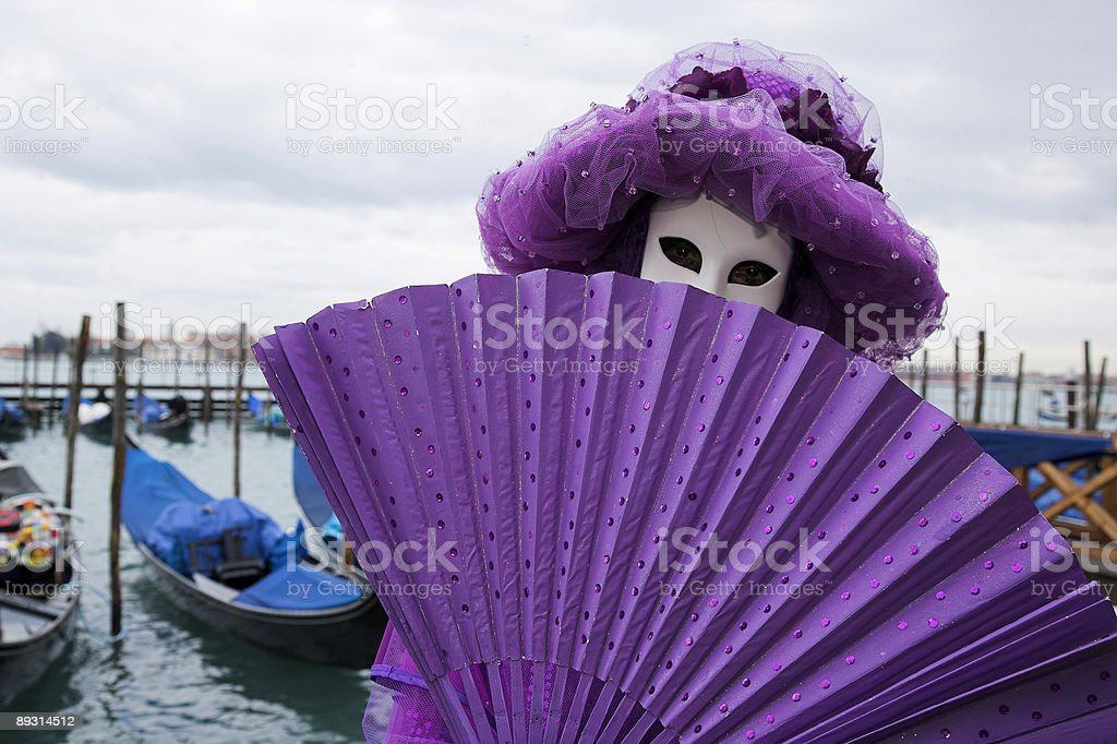 Mysterious female mask with fan at Grand Canal in Venice royalty-free stock photo