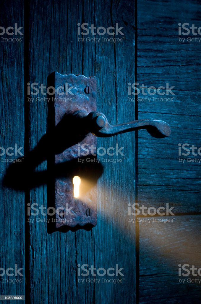 Mysterious Light Coming Through Antique Keyhole and Door stock photo