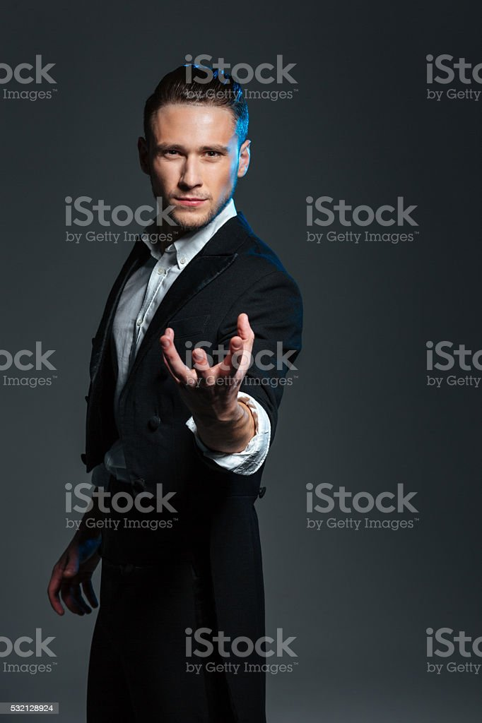 Mysterious magician holding something on palm stock photo