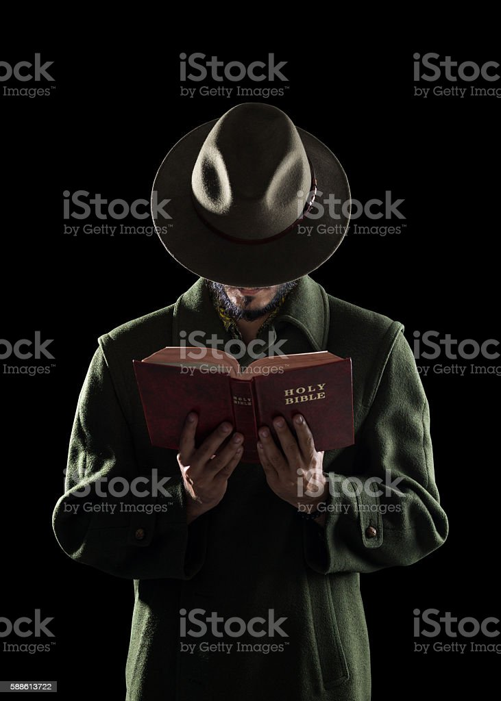 Mysterious Man Wearing Hat Reading Holy Bible In Dark stock photo