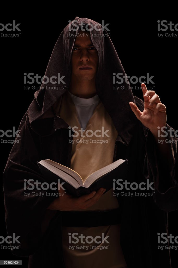 Mysterious monk holding a book and preaching stock photo