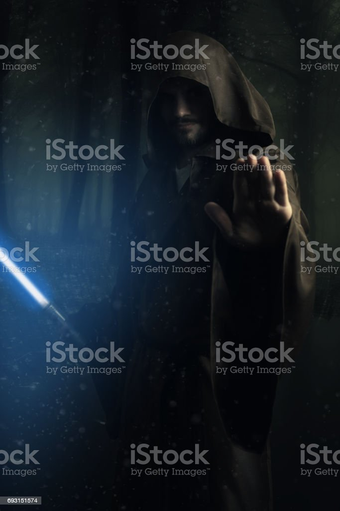 Mysterious warrior holding a lightsaber stock photo