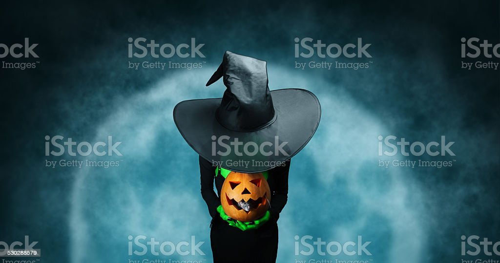Mystery Halloween witch with pumpkin stock photo