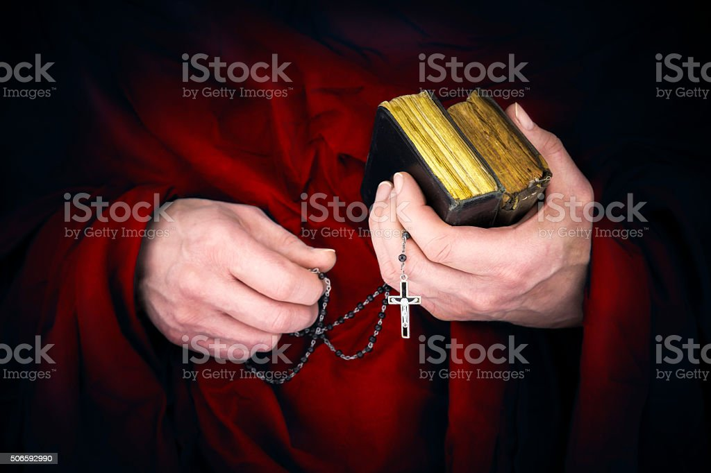 Mystery monk with a cape holding bibles and a black rosary stock photo