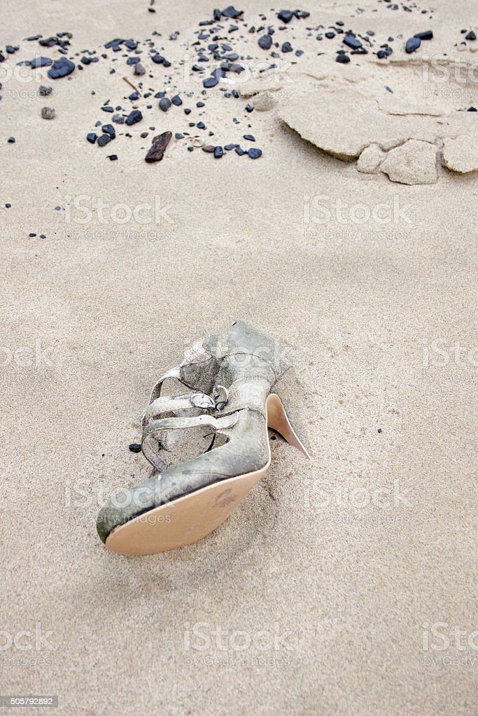Mystery of woman's shoe washed up on the shore stock photo
