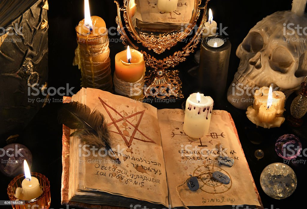 Mystic background with black magic book, candles and mirrow stock photo