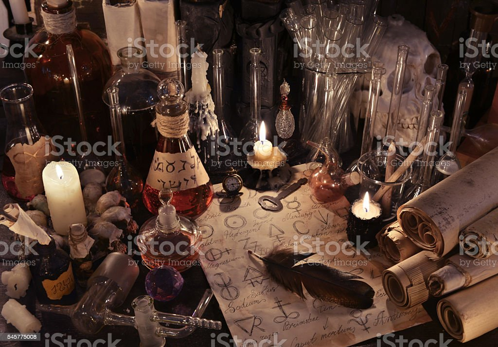 Mystic still life with alchemy paper, bottles and candles stock photo