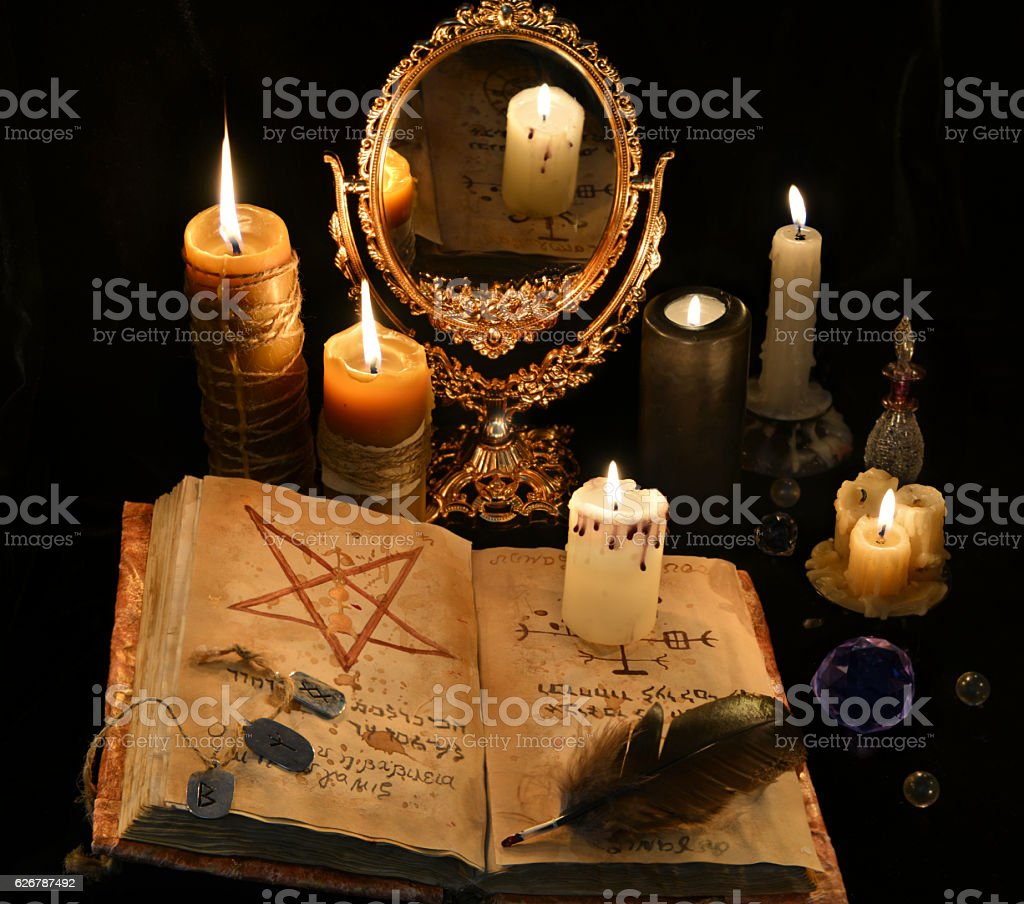 Mystic still life with black magic book, candles and mirrow stock photo