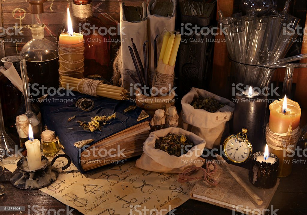 Mystic still life with healing herbs, candles and magic books stock photo
