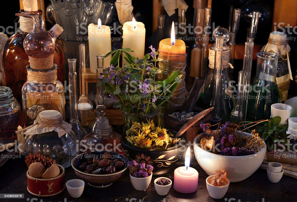 Mystic still life with herbs, bottles, candles and flasks stock photo