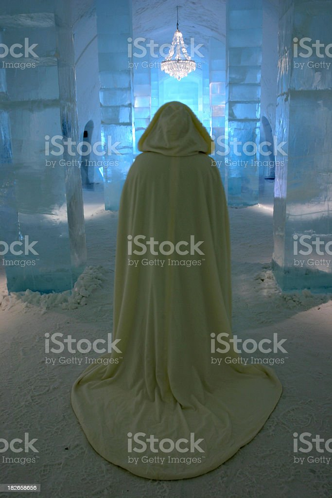 mystical caped maiden in an ice snow castle stock photo