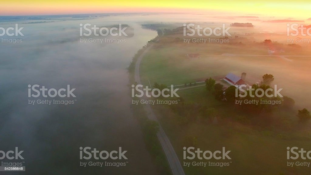 Mystical foggy country landscape with river, farms and homes. stock photo