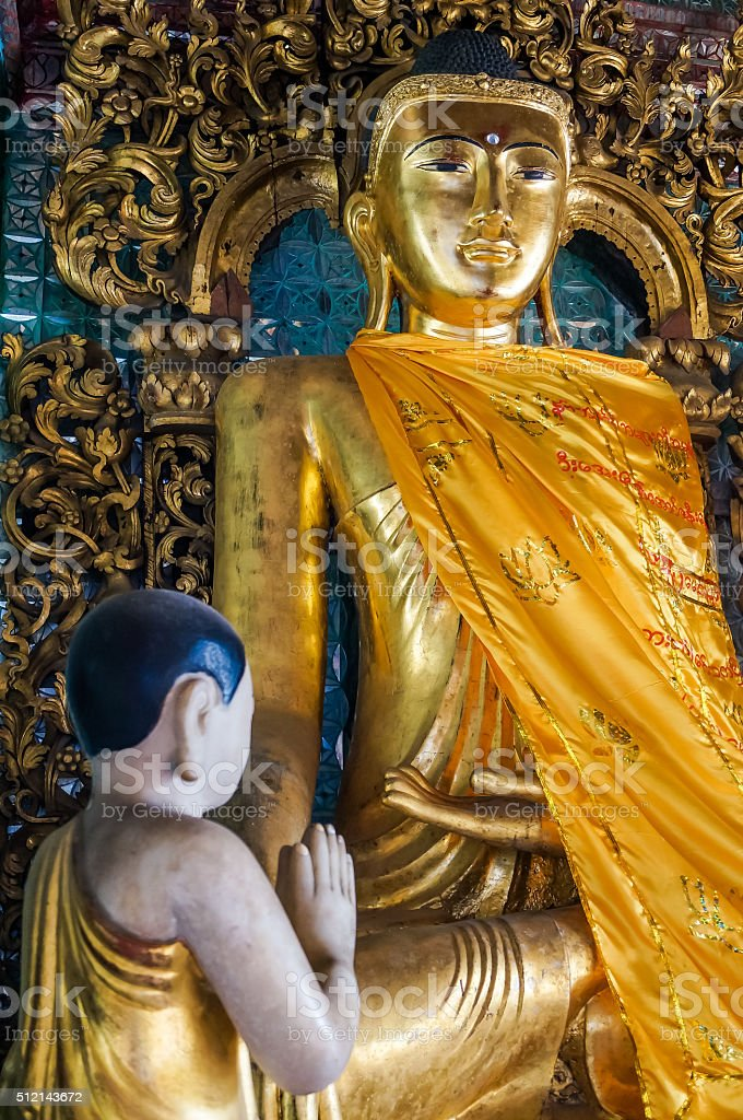 mystical golden Buddhastatue with praying monk in golden robe stock photo