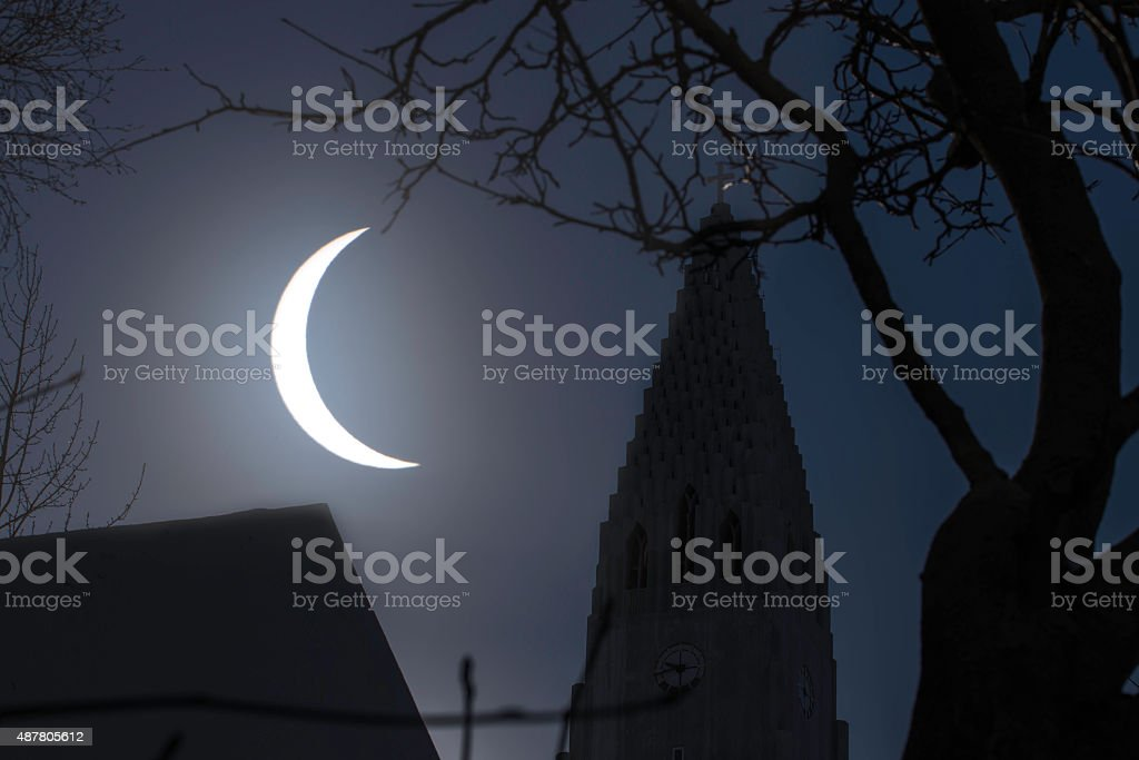 Mystical solar eclipse with church and trees in foreground stock photo