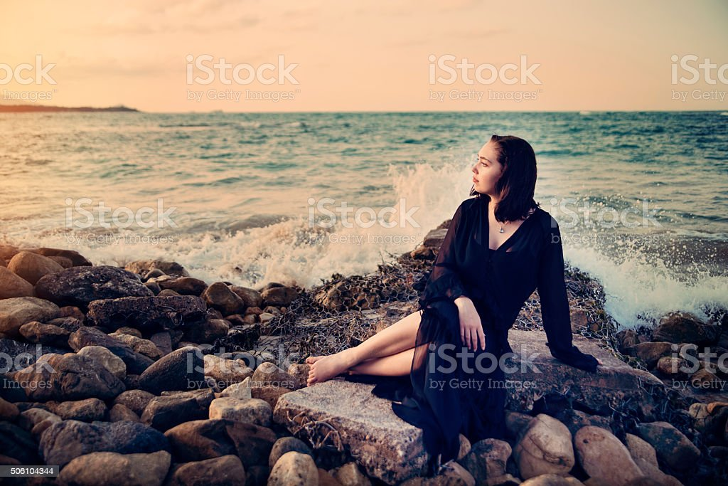 Mystical young woman at the beach, sunset, connecting with nature. stock photo