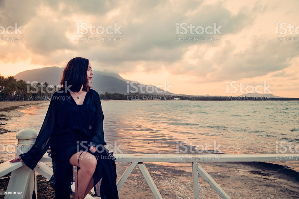 Mystical young woman sitting on a pier, sunset, enjoying nature. stock photo