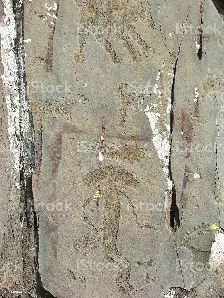 Mythical humanoid creature petroglyph carved in rocks stock photo